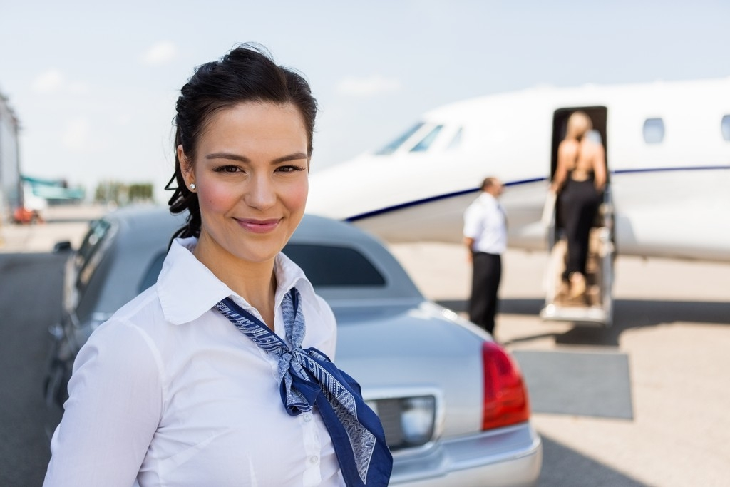 Portrait of beautiful airhostess standing against limousine and private jet at airport terminal