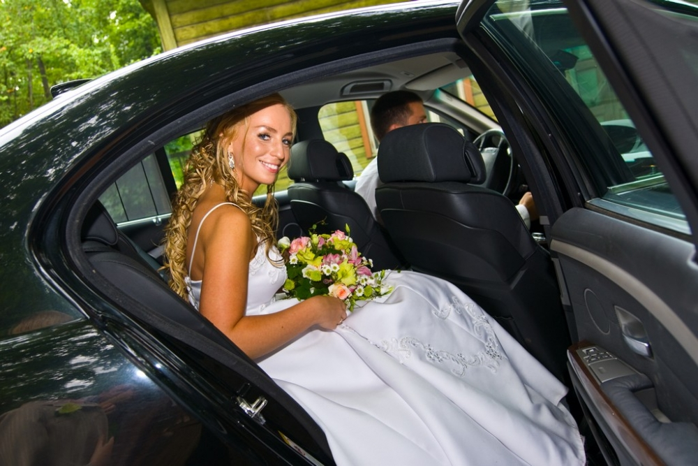 Bride sitting in a black wedding limousine.